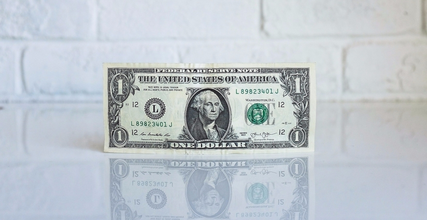 dollar bill balanced on its side